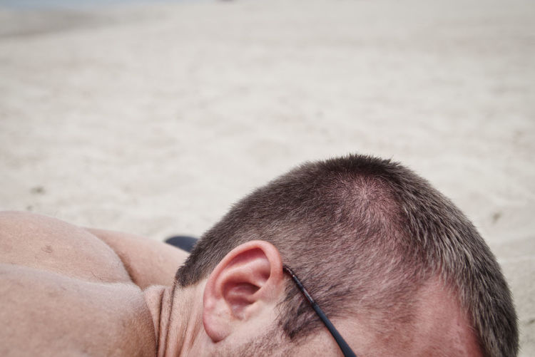 Close-up of man lying at beach