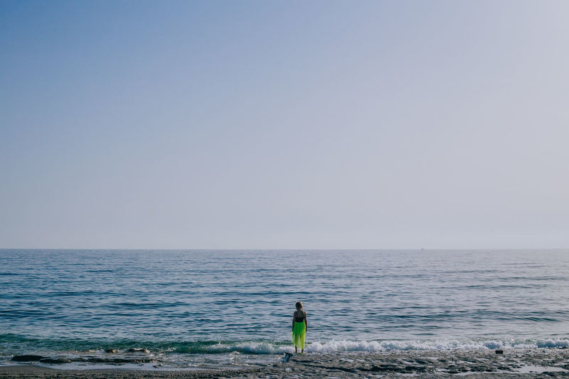 Rear View Of Girl Standing On Shore At Beach Against Clear Sky