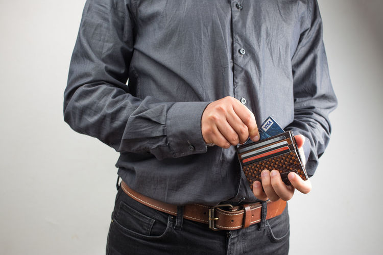 Young businessman, dressed in a dark blue shirt and dark blue trousers, standing and holding an open wallet with a credit card. In the background white wall. A man looks into an empty wallet Wallet Man Economy Background Money Back Pocket  Pants Wealth Savings Hand Business Isolated Empty Blue Clothing Concept Leather Purchase Spend Save White Closeup Cash Buy Fashion Finance Jeans Purse Financial Currency Elégance Success Consumption  Billfold Crisis Consume Capital Capitalism Denim Inside person Male Style Shirt Rear Black Arms Behind His