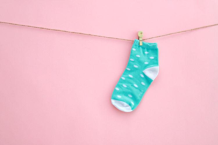 Close-Up Of Sock Hanging On Clothesline Over Pink Background