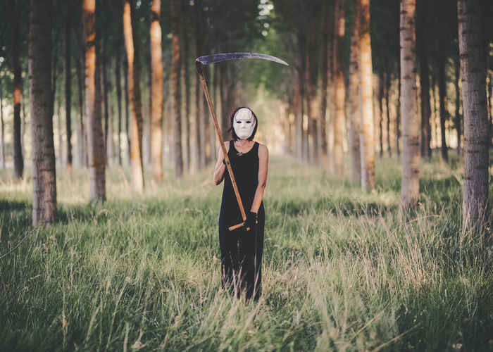 Full length of woman wearing mask and holding scythe standing in forest