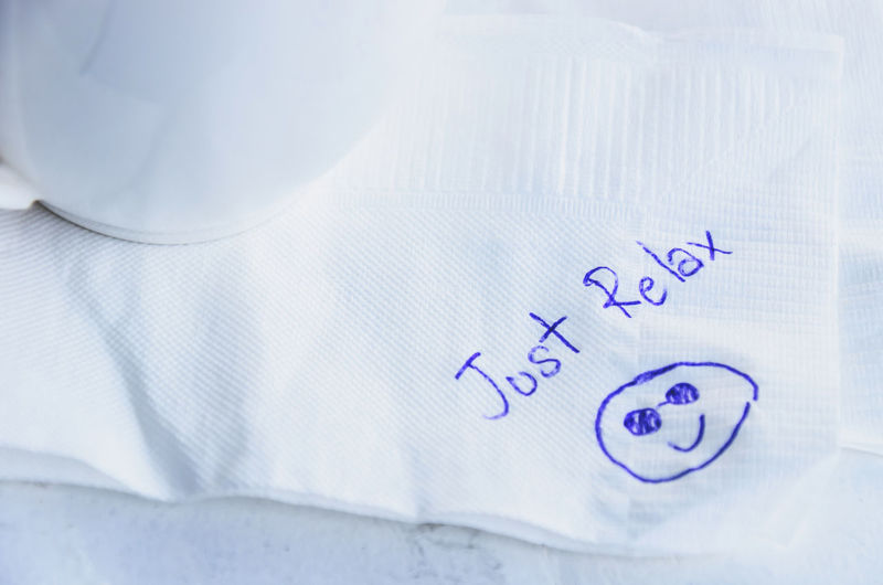 High angle view of text with smiley face on tissue paper