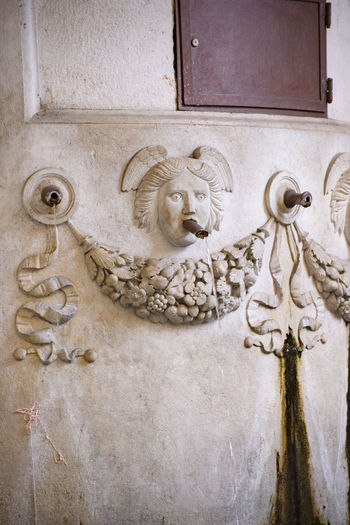 Close-up of old sculpture against wall