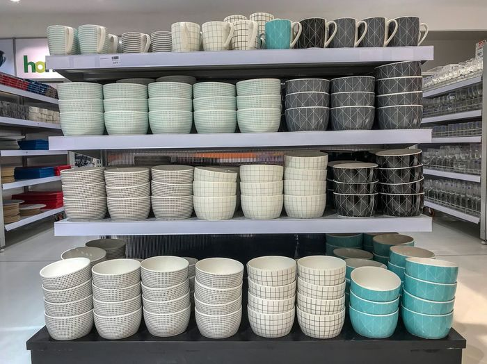 Various crockeries on shelf for sale in store