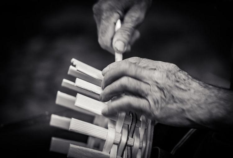 Cropped hands of man making wicker basket