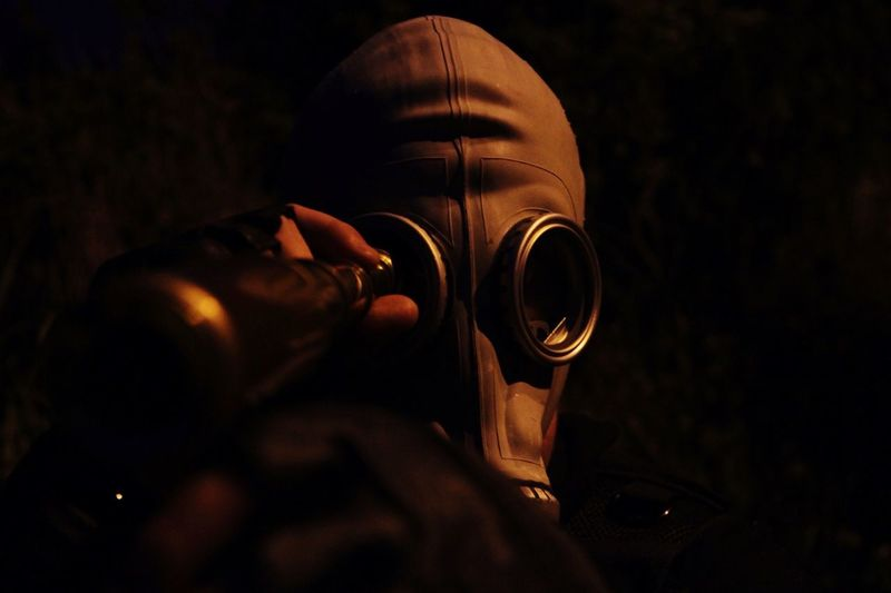 Close-up of person wearing protective mask in darkroom
