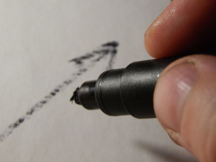 Close-up of person holding felt tip pen on paper