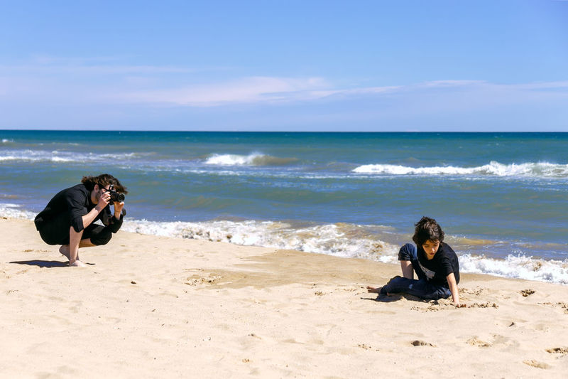 Professional photographer with photo camera shooting teenage boy lying on sandy beach of ocean coast Sea Beach Land Water Sand Leisure Activity Sky Nature Horizon Horizon Over Water Day Outdoors Photographer Boy Man Photography Fun Professional Teenager Brothers Posing Sunny
