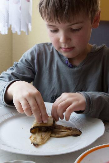 Boy Folding Beef Kebab In Eggplant Slices In Kitchen