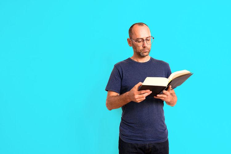 Full length of man standing against blue background