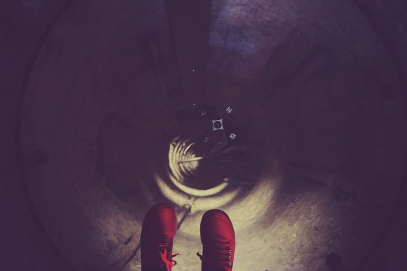 Low Section Of Woman Feet With Red Shoes Hanging Against Manhole