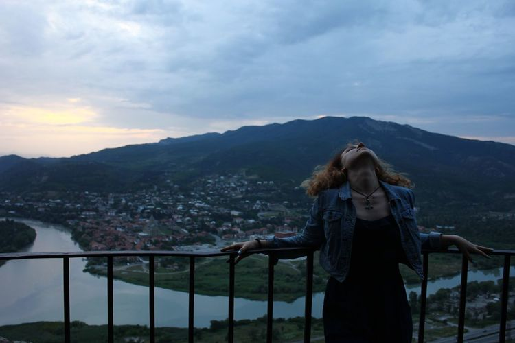 Woman at observation point against mountain in town