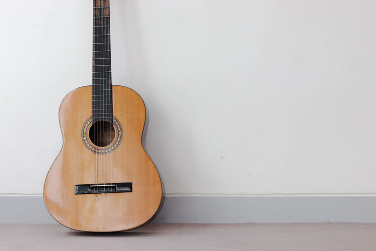 Music Instrument Guitar Musical Instrument String Instrument Music Guitar Musical Equipment Wall - Building Feature Indoors  String Wood - Material Acoustic Guitar Arts Culture And Entertainment Still Life Musical Instrument String No People Copy Space Brown Single Object Home Interior Close-up Flooring