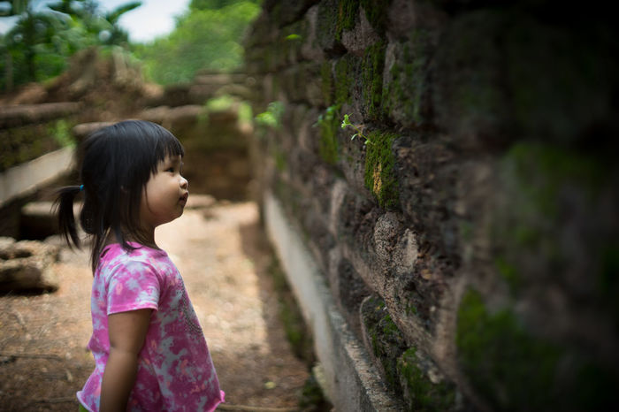 little girl looking a grass on the old rock wall Grass Asian Style Conical Hat Black Hair Casual Clothing Child Childhood Contemplation Day Females Focus On Foreground Girls Hair Hairstyle Innocence Looking Nature Old Rock Wall One Person Outdoors Portrait Photography Profile View Side View Standing Waist Up Women