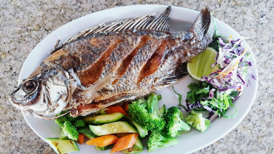 High angle view of fish and vegetable served on table