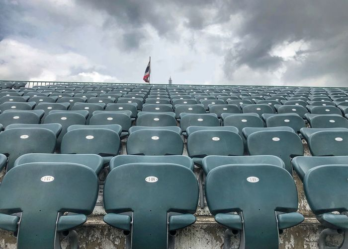 Seats available Cloud - Sky Sky In A Row Seat Day Side By Side One Person Overcast Chair Nature Empty Order Real People Outdoors Repetition Lifestyles Arts Culture And Entertainment Leisure Activity