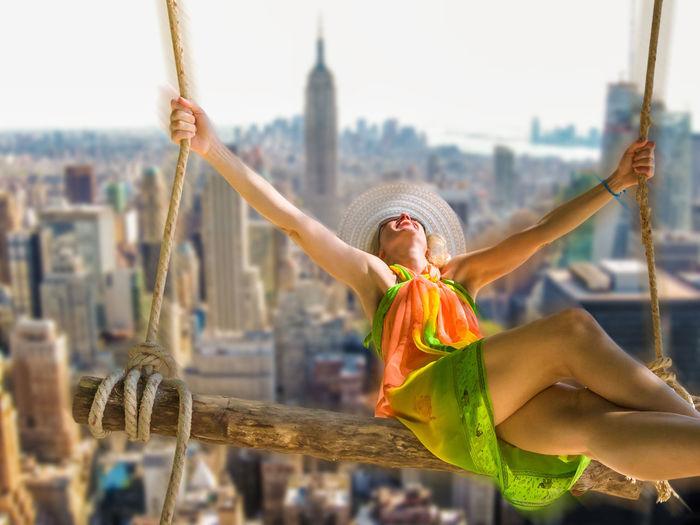 Digital composite image of woman swinging against manhattan