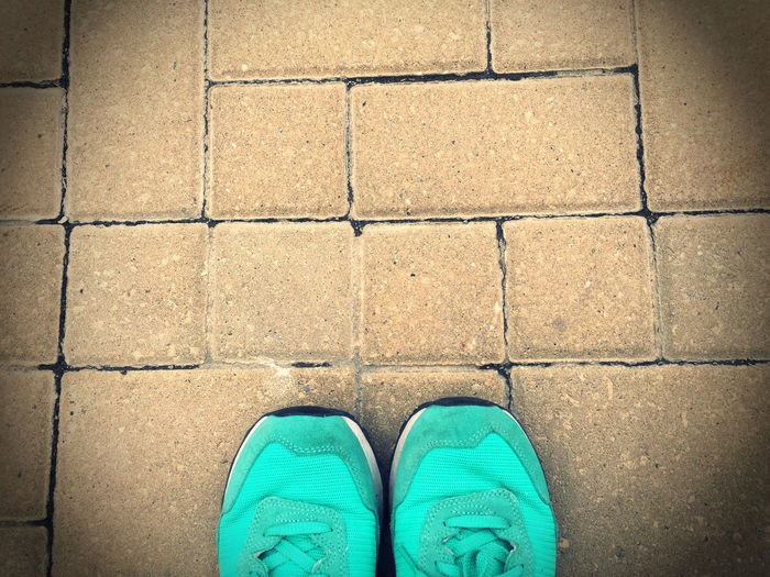 Low section of person wearing shoes while standing on paving stone