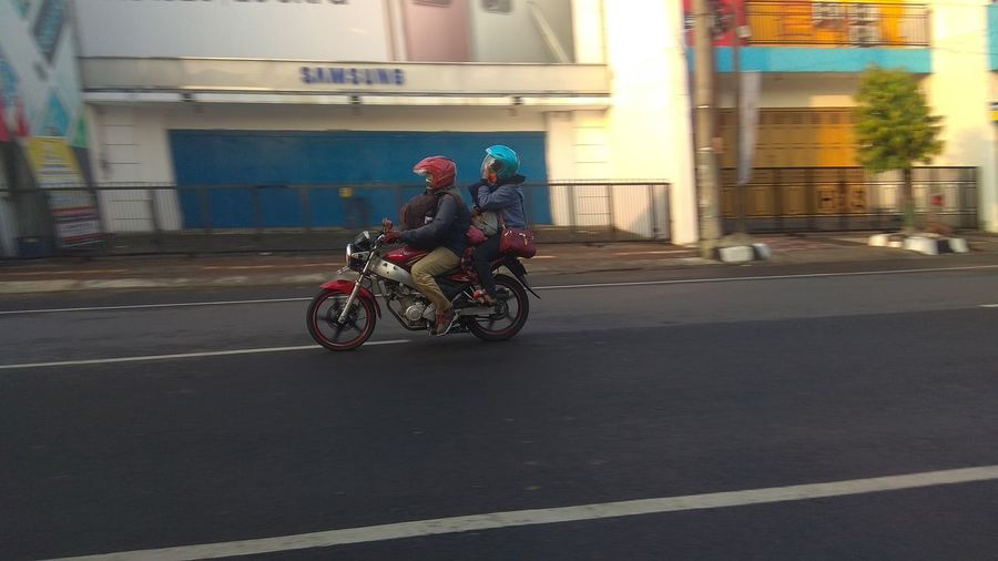 Bicycles riding motorcycle on road in city