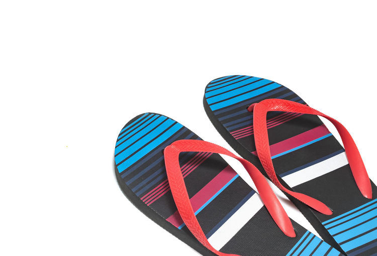 High angle view of multi colored slippers on white background