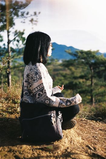 Side View Of Woman Sitting In Lotus Position On Landscape