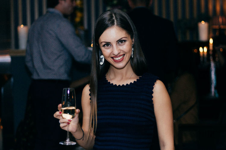 Portrait of smiling young woman having wine in party