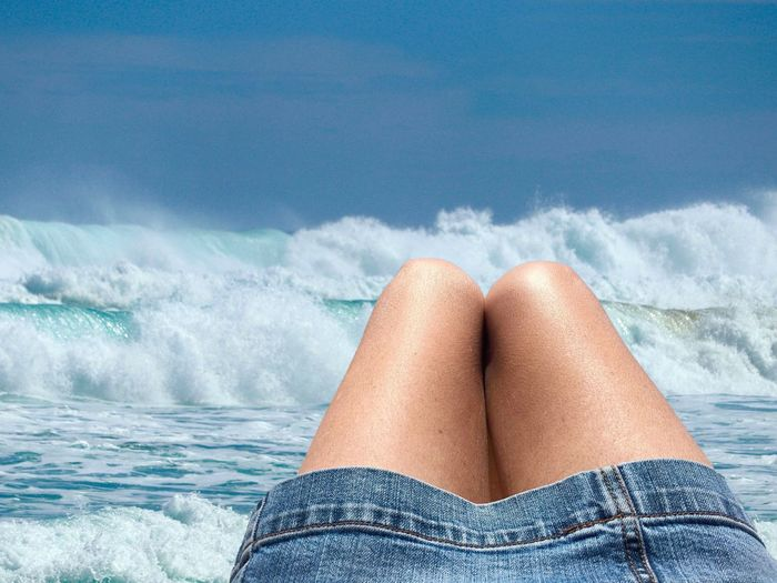 Midsection of woman in sea against sky