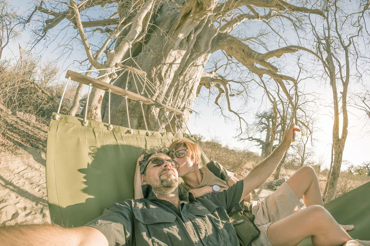 High angle view of couple lying on hammock by tree in sunny day