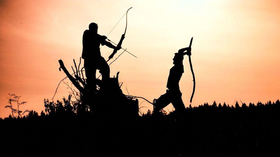 Silhouette men fighting on field against orange sky