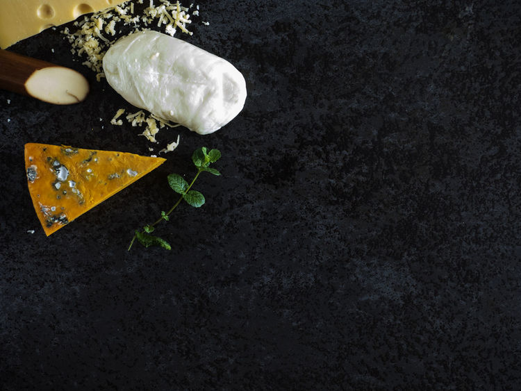 Fresh pieces of cheese (Mozzarella, roquefort, Maasdam) on the stone table Background Black Cheese Food France Fresh Ingredient Italy Maasdam Mint Mozzarella Netherlands No People Pieces Roquefort Slate Switzerland Table