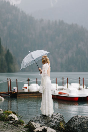 Beautiful young woman bride in a boho dress and with an umbrella stands in the rain in nature
