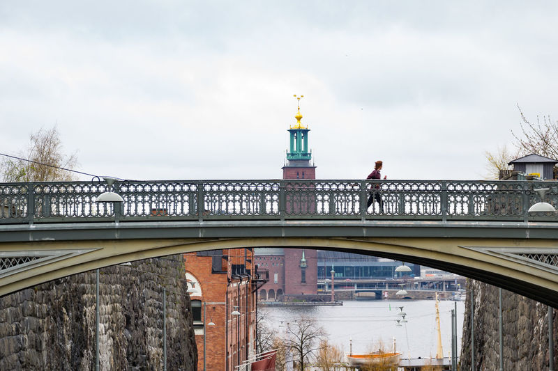 Person Jogging Over Bridge Against Stockholm City Hall