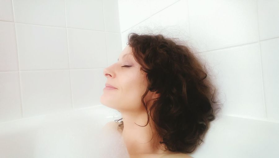 Happy Woman Relaxing In Bathtub At Home