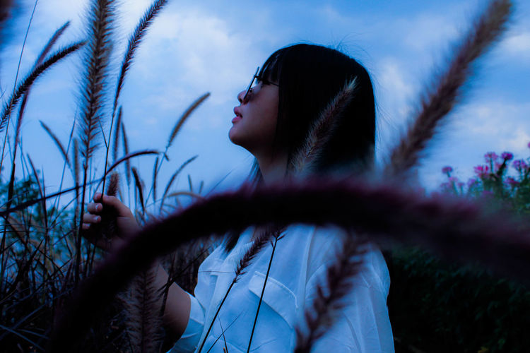 Woman looking away amidst plants against sky