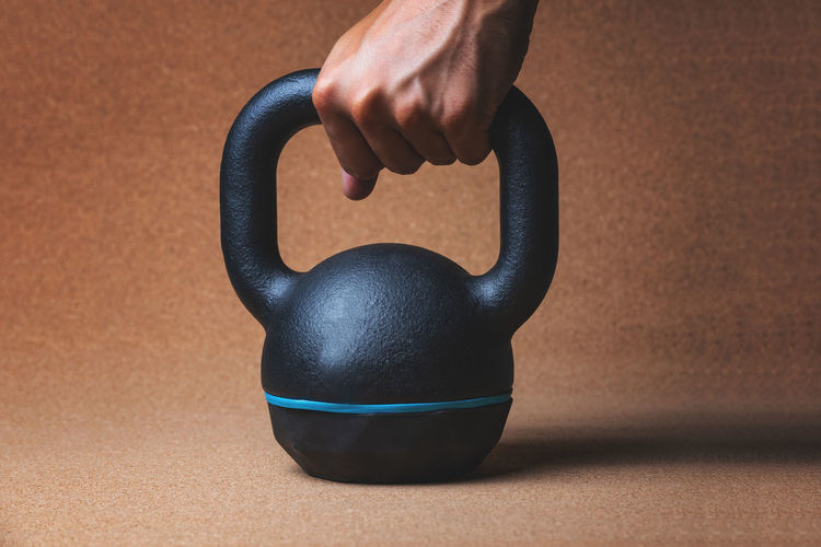 Close up view of a hand holding a kettlebell - studio shot Black Color Blue Body Part Brown Close-up Fit Fitness Focus On Foreground Gym Hand Healthy Lifestyle Holding Human Body Part Human Hand Indoors  Kettlebell  Muscles Muscular Build One Person Single Object Sport Strength Studio Shot Table Wall - Building Feature