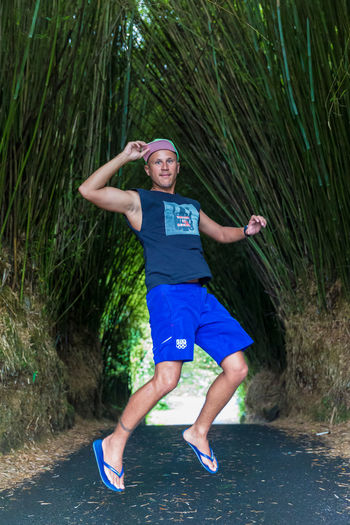 Portrait Of Young Man In Mid-Air Over Road Amidst Bamboo Trees