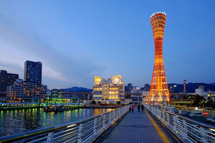 Low Angle View Of Illuminated Kobe Port Tower And Buildings Against Sky At Dusk