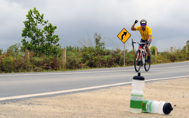 Bottles against male cyclist gesturing while cycling on road against sky
