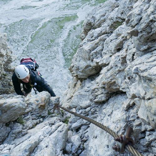 High angle view of woman climbing rock