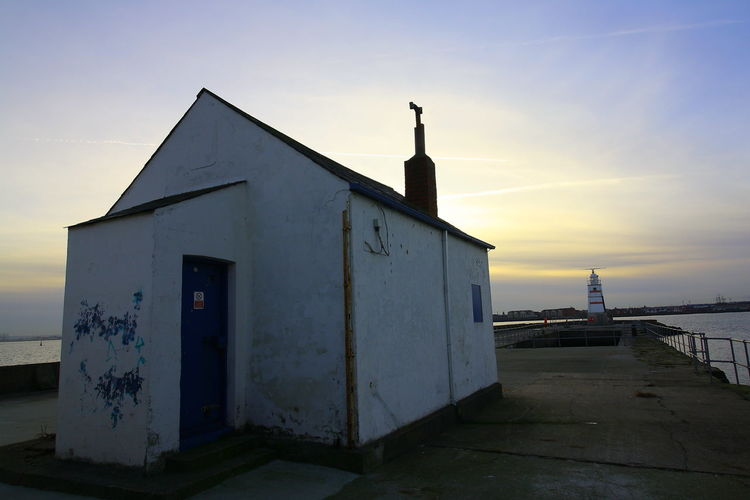 OUT AND ABOUT IN HARTLEPOOL Sky Sunset Architecture Built Structure Building Exterior Building Sea Nature Water Cloud - Sky No People Direction Outdoors Land Wood - Material Guidance Beach Orange Color Safety
