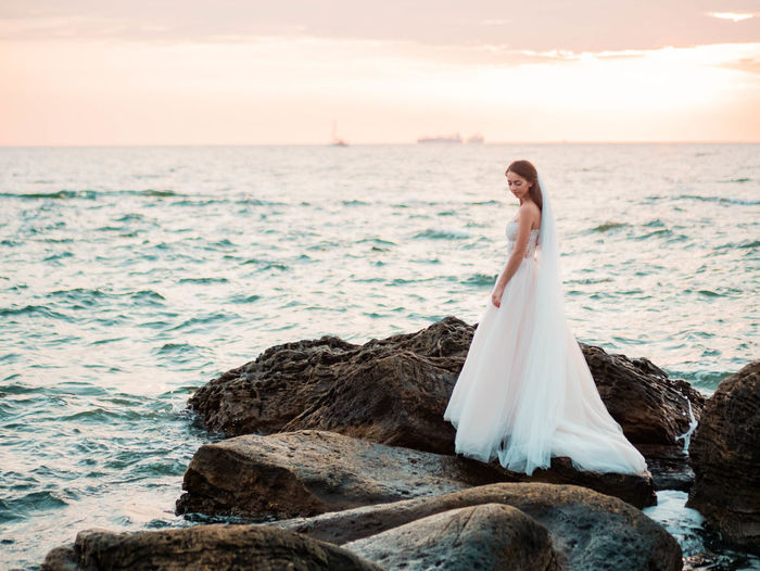 Full Length Of Bride Standing On Rock In Sea Against Sky During Sunset