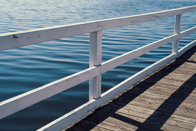 Part of wooden pier in front of blue water