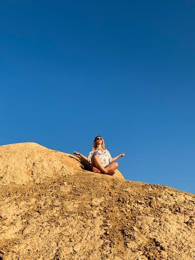 Low angle view of woman meditating on rock formation against clear sky