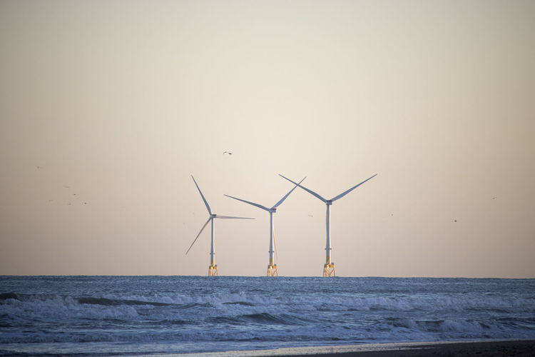 Wind turbines by sea against sky during sunset