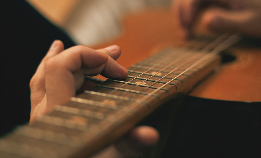 Close-up of hands playing guitar against blurred background