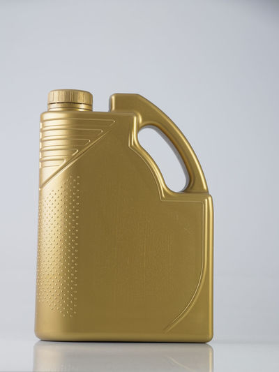 golden canister with engine oil on white background Golden Lubricant Label Isolated Gasoline Container Industry Engine Oil Object Package Packaging Auto Automobile Motor Oil Full Fuel Canister Bottle Blank Clean Handle Gallon Unlabelled White Background Gold Colored Studio Shot Single Object