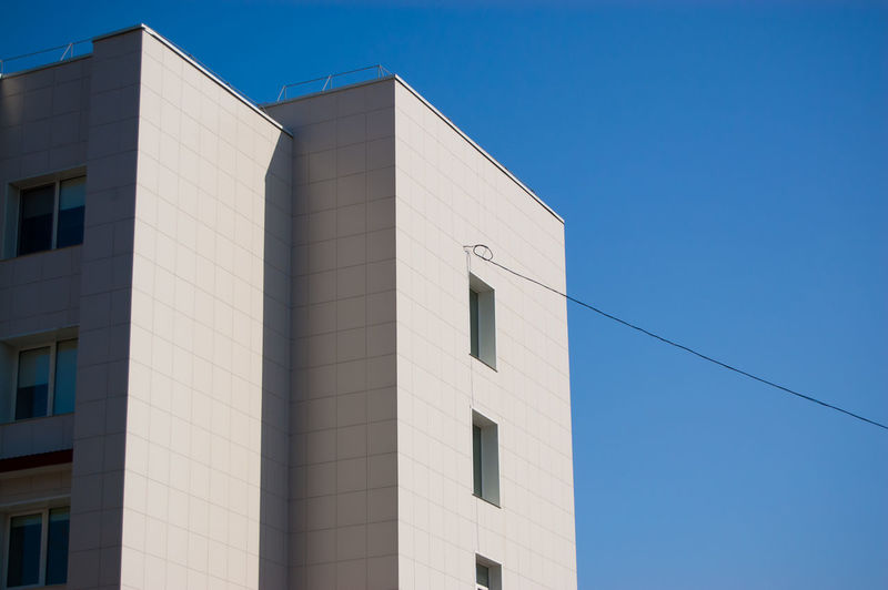 Modern building with electric wire against a blue sky.