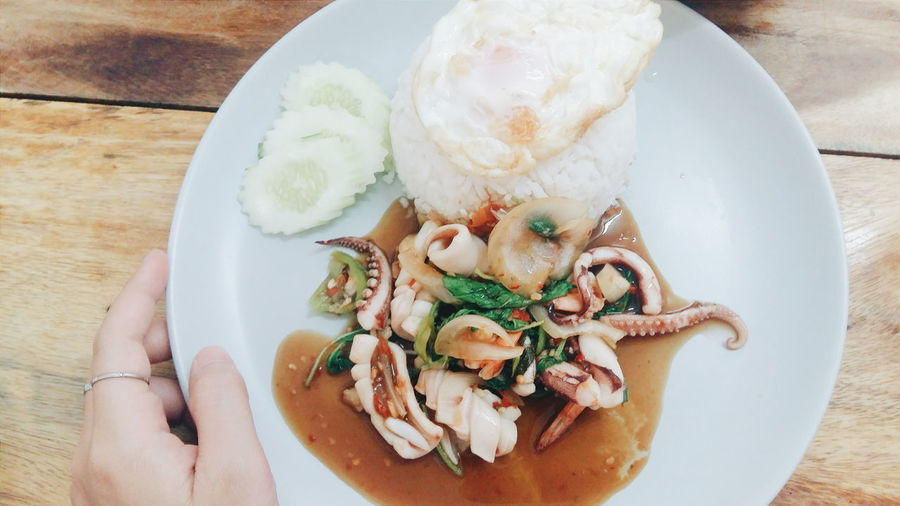 Cropped image of hand holding octopus in plate
