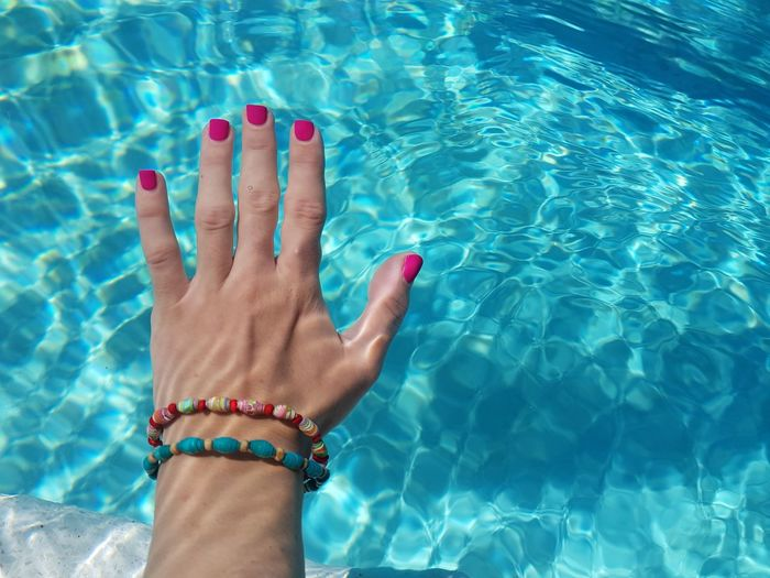 Cropped hand of woman in swimming pool