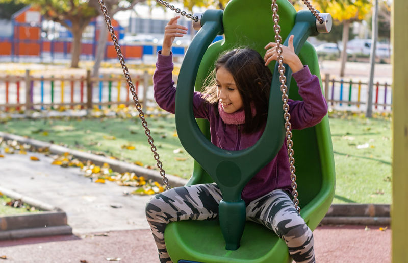Girl sitting on swing at park